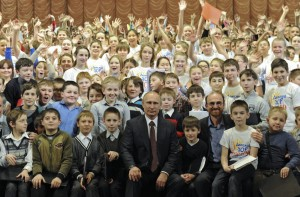 Russian President Putin poses for a picture with members of a children's choir during his visit to the Mariinsky Theatre in St.Petersburg